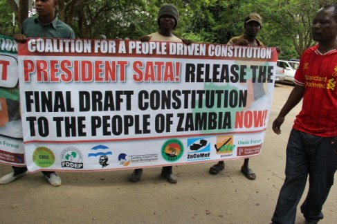 People holding a banner demanding that President Sata releases the draft constitution. Picture used with permission of The Zambian Voice.